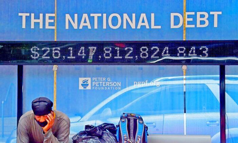 A man waits at a bus stop that displays the official national debt of the United States in Washington on June 19, 2020. The nonprofit Truth in Accounting says the actual national debt is more than four times the official figure. (Olivier Douliery/AFP via Getty Images)